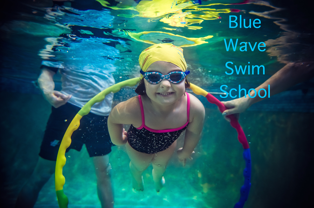 A toddler swims though underwater hoop with confidence