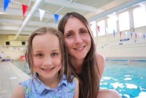 A happy parent with her child says thank you at Blue Wave Swim School in London