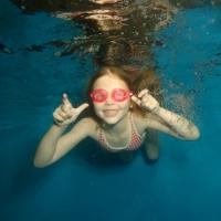 A school-aged child swims underwater at Blue Wave Swim School