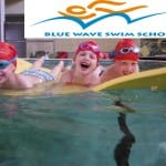 Three swimmers have fun on a big float in their lessons