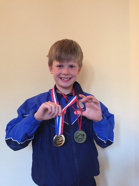 One of the advanced swimmers at Blue Wave Swim School showing his medal