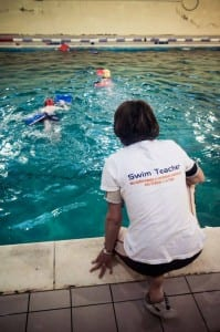 Swimming Teacher instructing children .