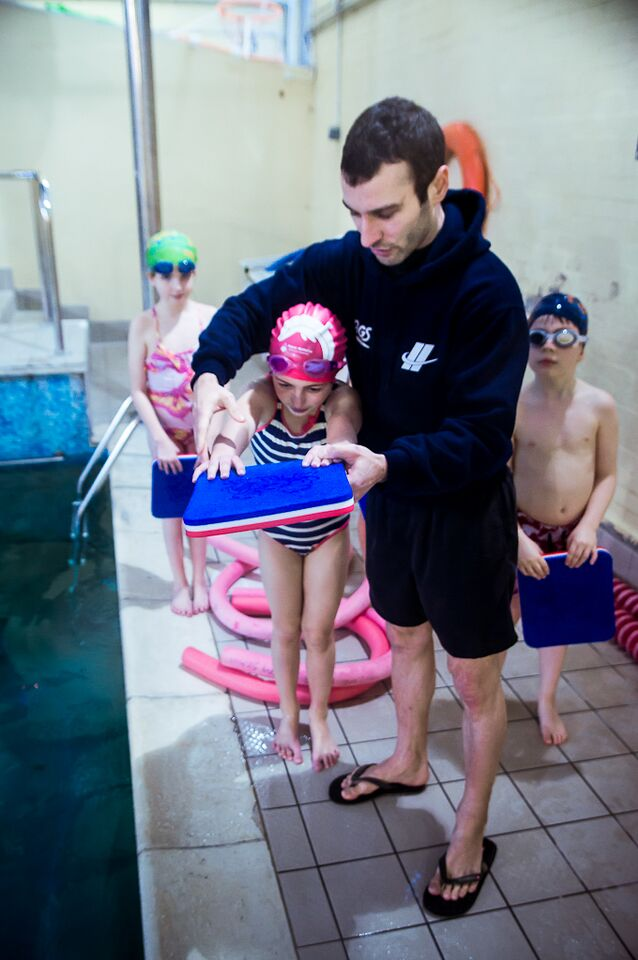 A Swim England qualified swim teacher teaches swimming at Blue Wave Swim School in Wimbledon, London