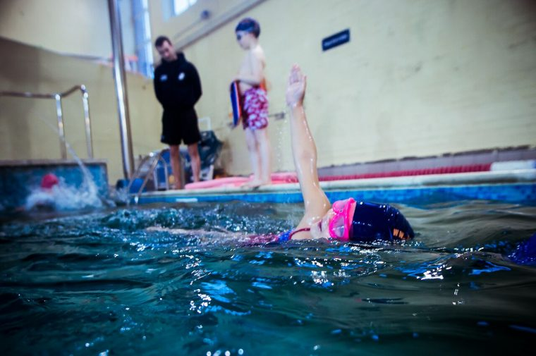 Group swimming and a child swims front crawl in group lessons at Blue Wave