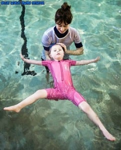 A child learning to float in swimming lessons in Wimbledon