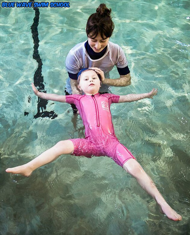 a pre-school aged child floats on her back with the help of a swim instructor.