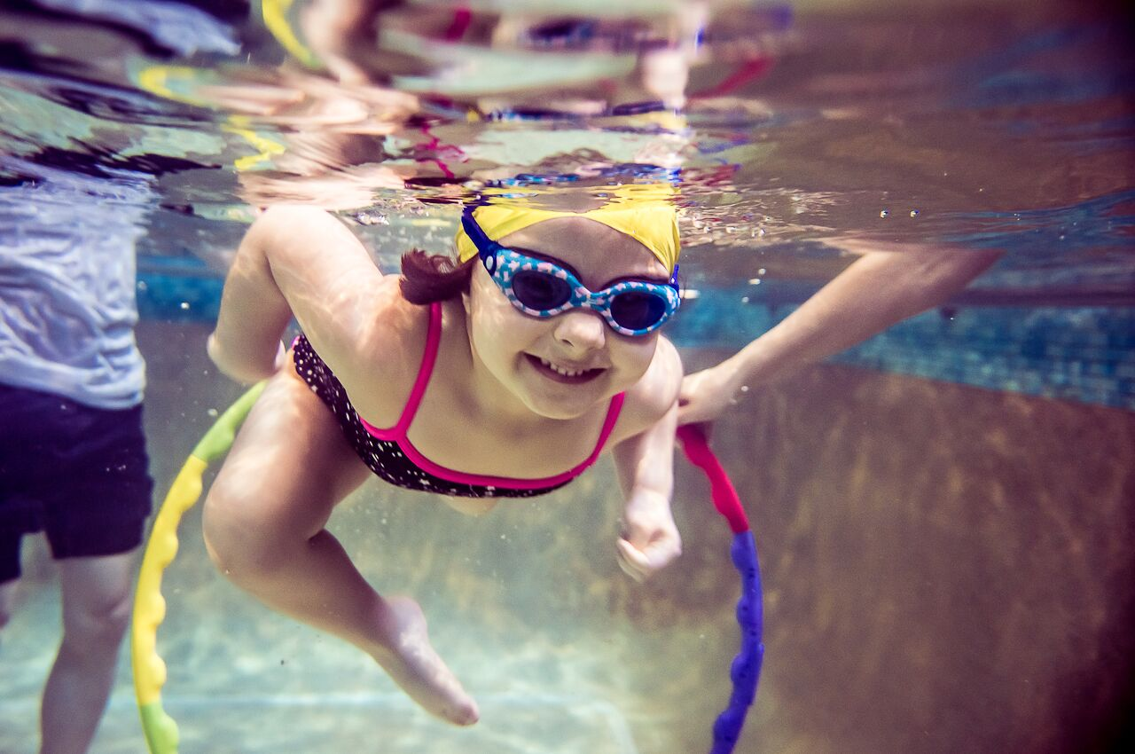 Toddler swimming through a hoop underwater at Blue Wave