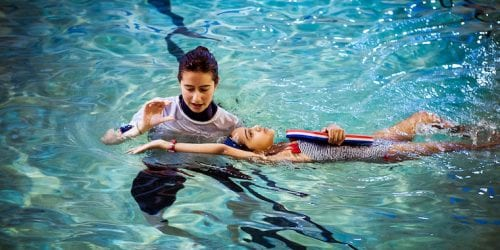 teaching private swimming lesson to a child