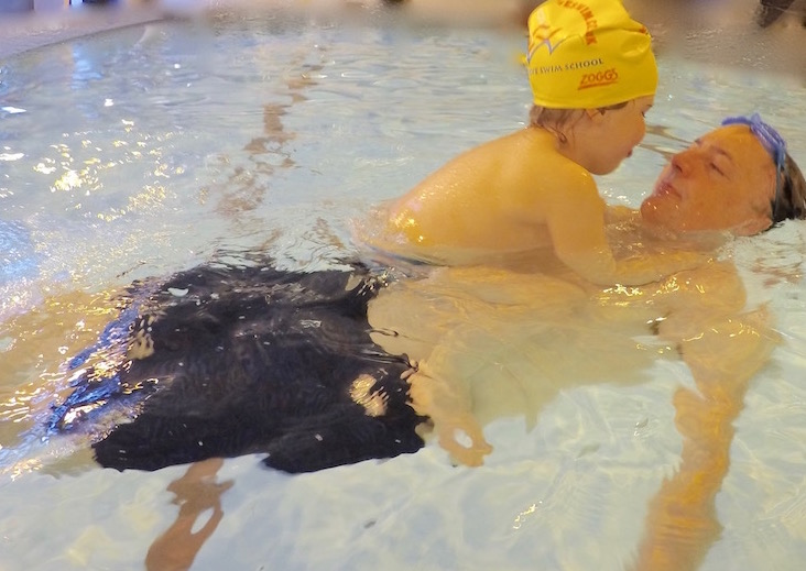A father and daughter swimming together and relaxing in water