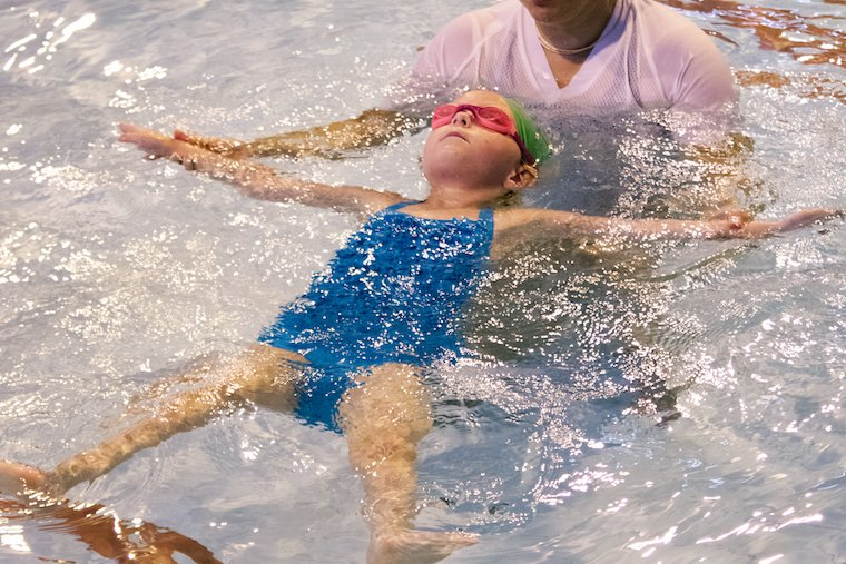 A child is floating on her back in water with confidence