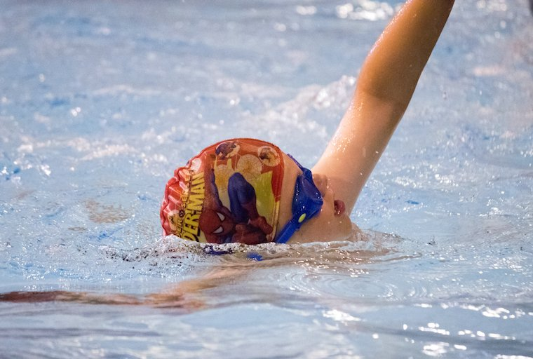 A boy swims front crawl at blue wave swim School's lesson in London