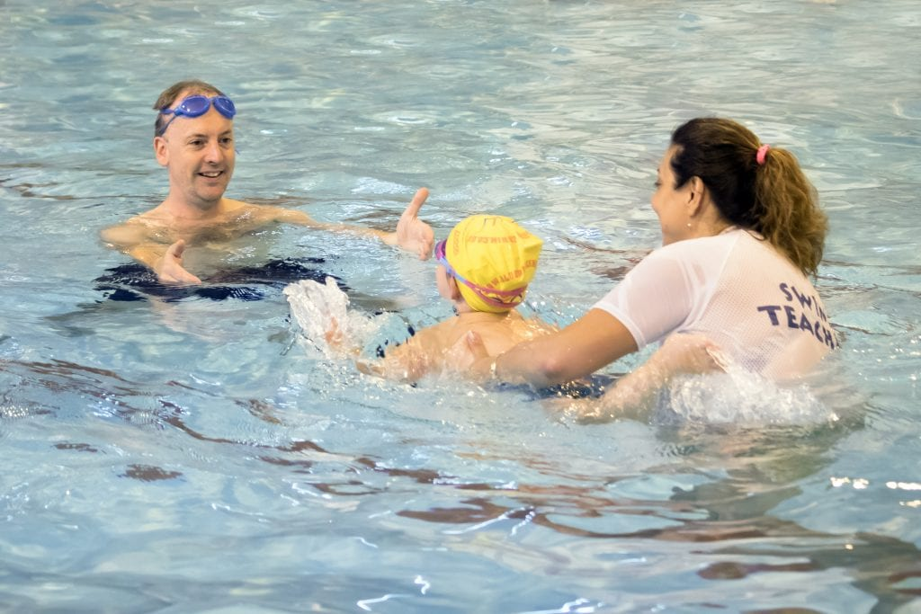 a child learning to swim with a swim teacher