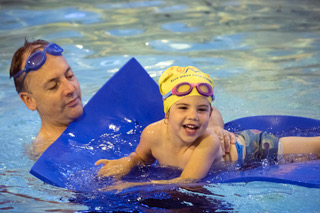 toddler learning to swim with her dad