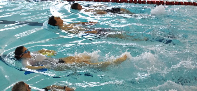 Adults learning to swim backstroke in swimming lessons