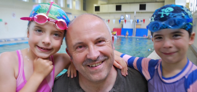 A-father-with-his-school-aged-twins-at-Saturday-swim-lesson-at-Blue-Wave-Swim-School