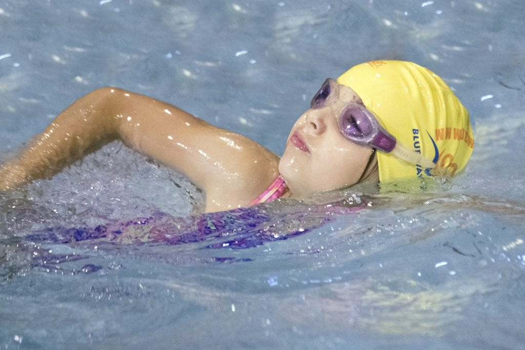 A child swimming confidently at Blue Wave Swim School