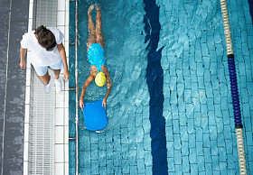 A Swim instructor teaching a child to swim