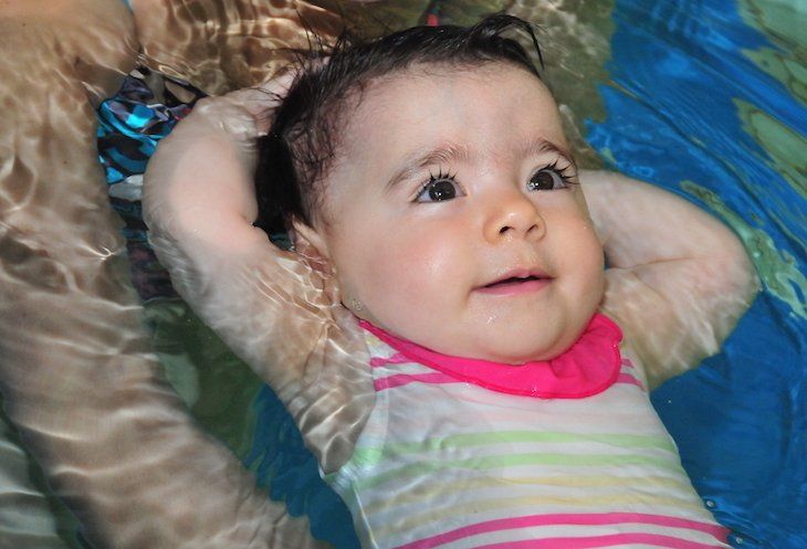 baby is learning back floating in water in a swimming lesson