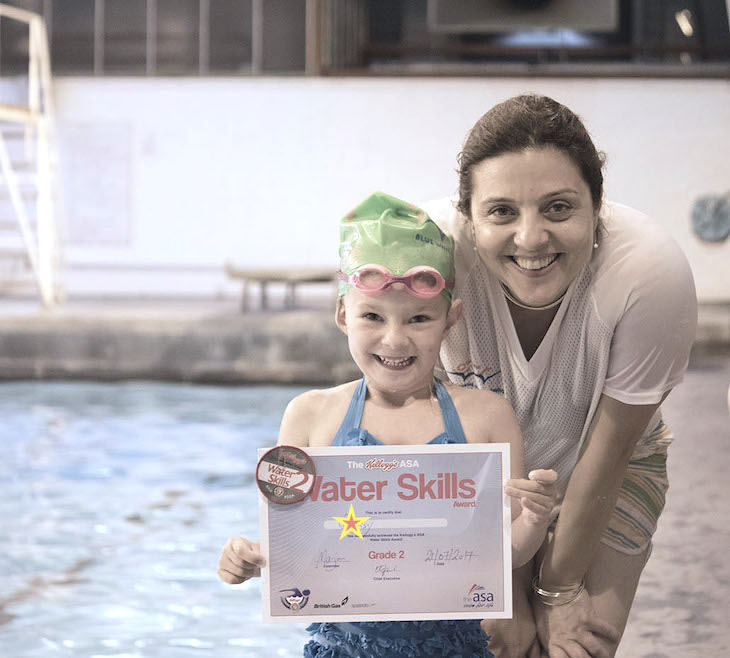A swimmer at Blue Wave Swim School with her Swim England swimming badge and certificate