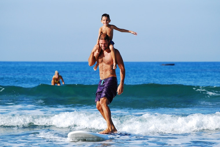 A happy child swimming and enjoying learning to surf with his father in sea