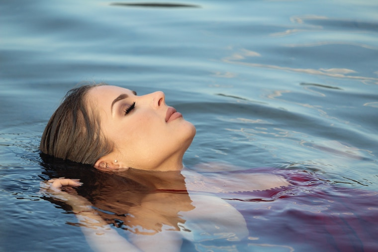A female swimmer is relax in water