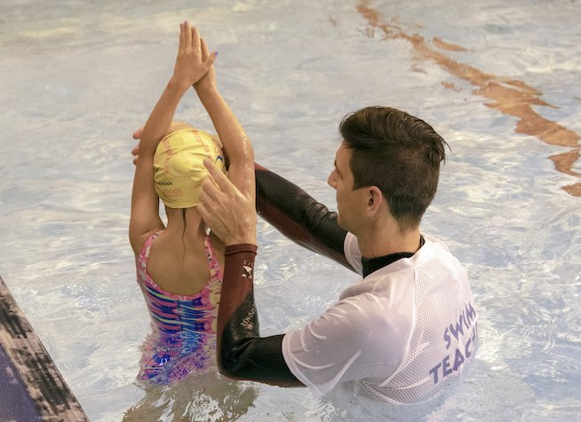 A swimming teacher is teaching a private swimming lesson
