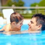 Father and son swimming in a swimming pool on holiday