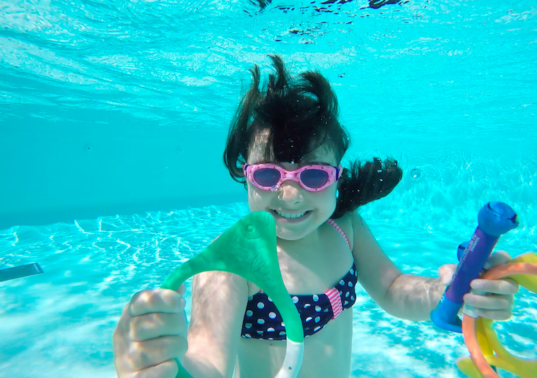 a happy girl swims under the water in summer in an outdoor swim pool