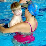 An autistic child and his swim teacher in a swimming lesson