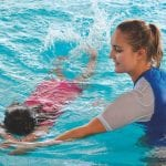 happy swim instructor in water teaching a child to swim
