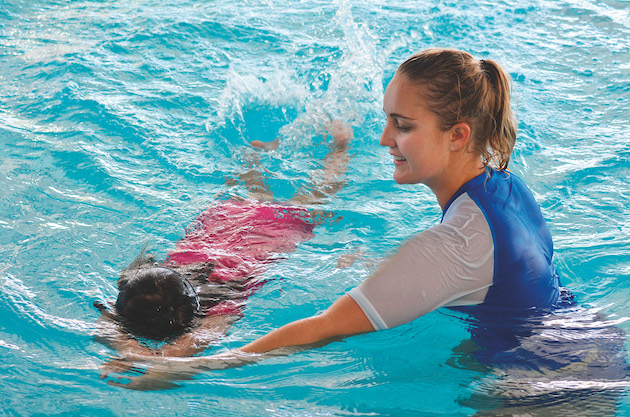 A happy swim teacher is teaching a child to swim