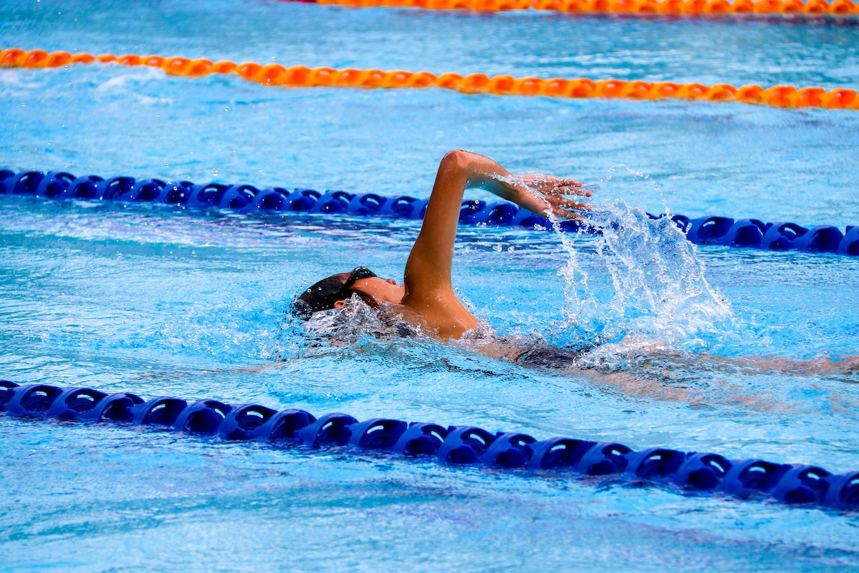 an school aged child swimming in a pool