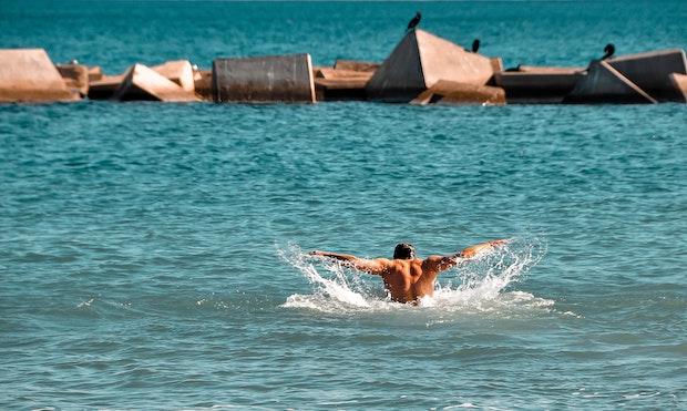 open water swimming by a male swimmer in sea