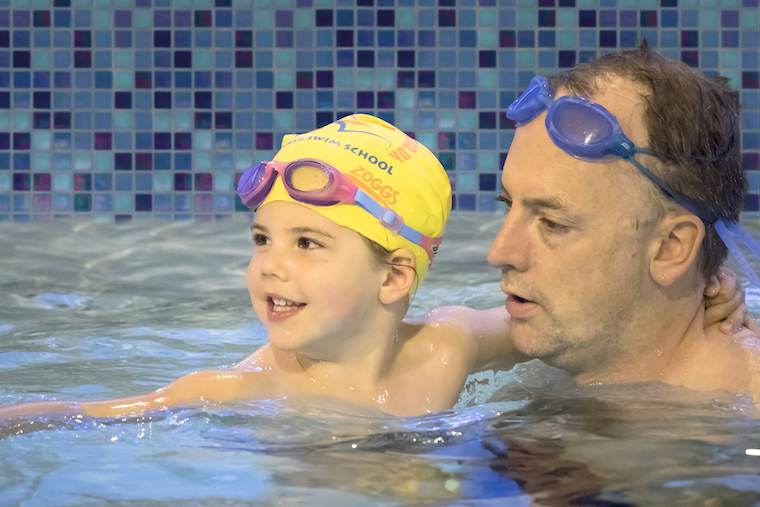 A father with his toddler at toddler swim class at Blue Wave Swim School